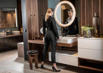 HOLTER_dunkles modernes Badezimmer mit huebscher Frau vor dem Spiegel